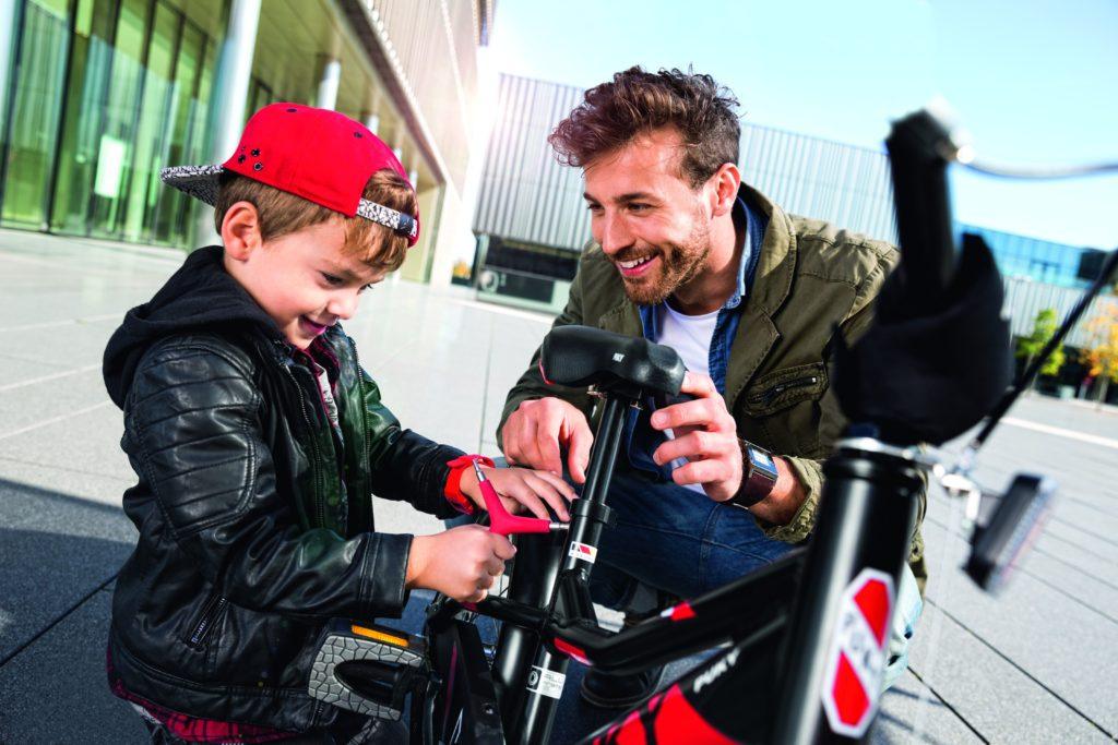 Père et son fils en train de régler la selle du vélo enfant