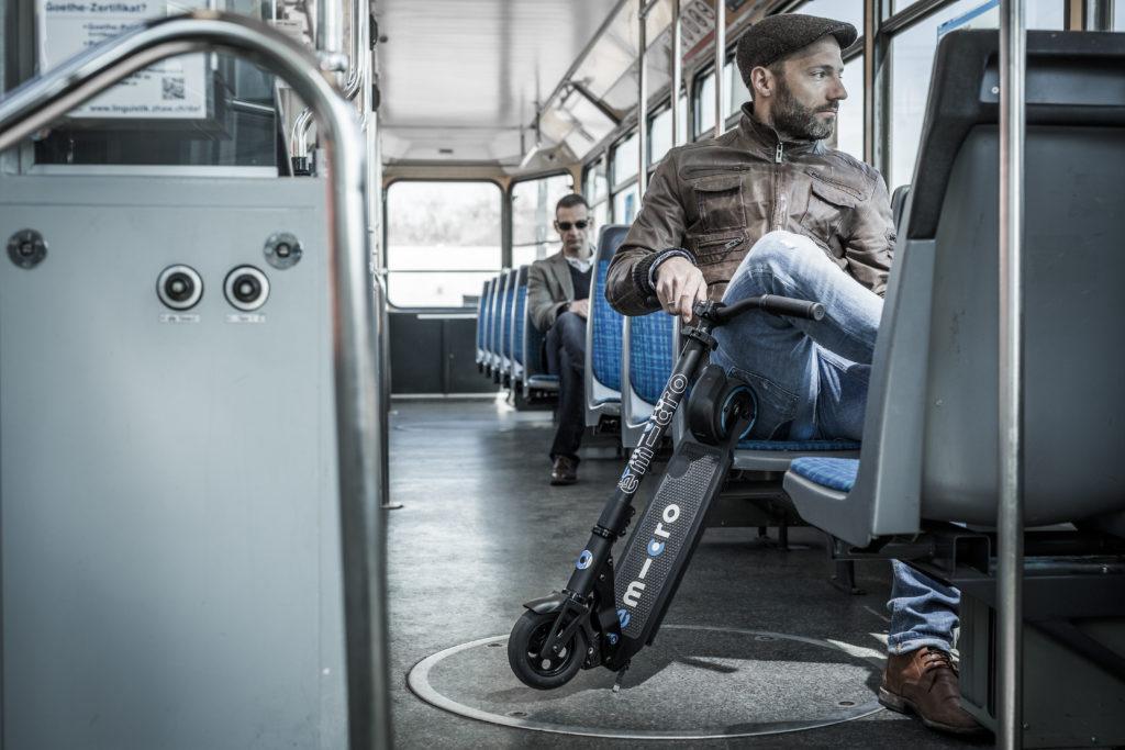 Homme dans le bus avec une trottinette electrique pliee