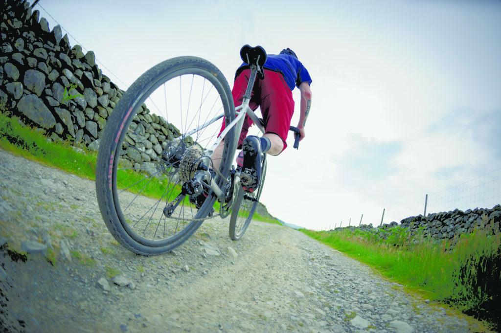 Cycliste roulant sur un vélo gravel sur une route non revêtue