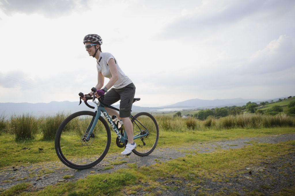 Femme roulant sur un gravel bike sur un chemin