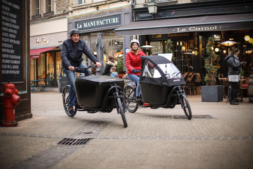 Deux cyclistes sur des biporteurs dans une ville de France