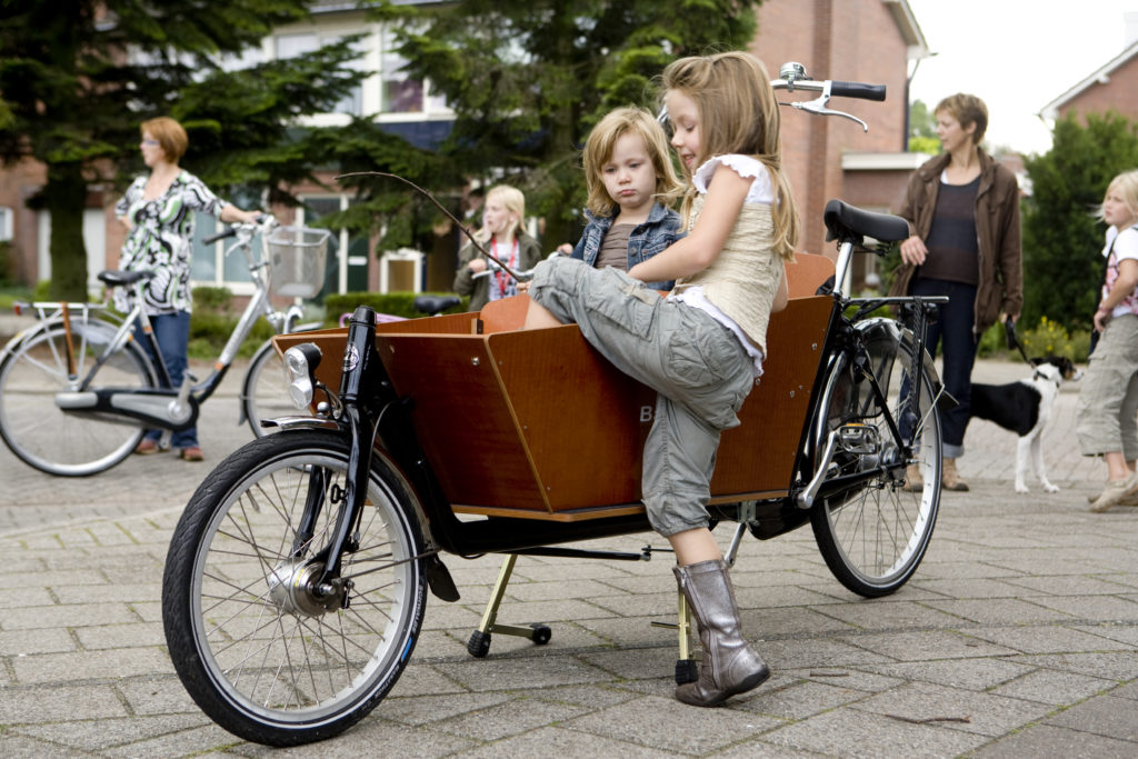 Enfant montant seule dans la caisse d'un vélo cargo à deux roues