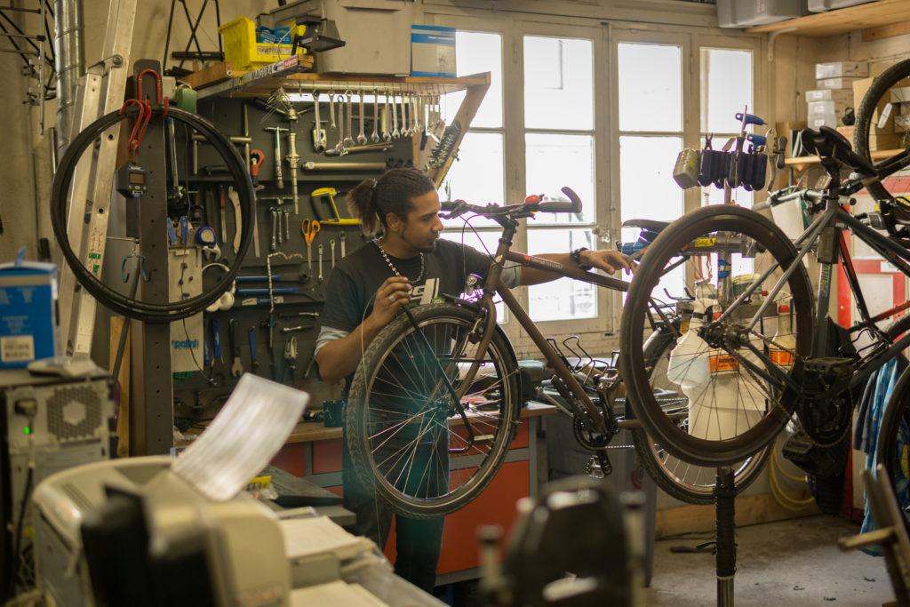 Mécanicien dans l'atelier de Cyclable Montpellier centre, travaillant sur un vélo trekking