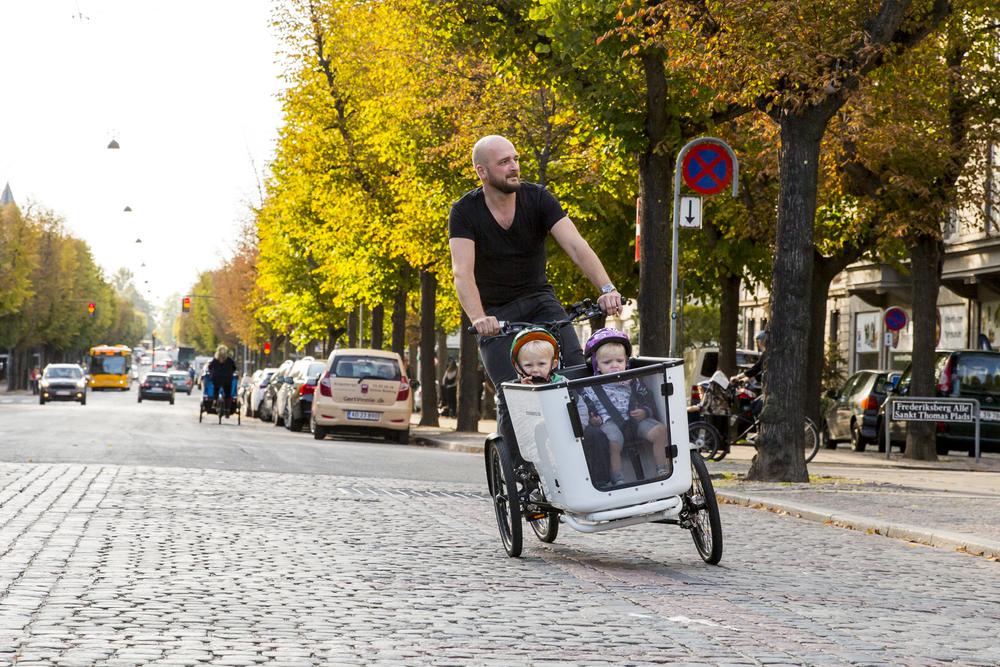 Père avec ses deux enfants en train de rouler en ville sur un triporteur pendulaire
