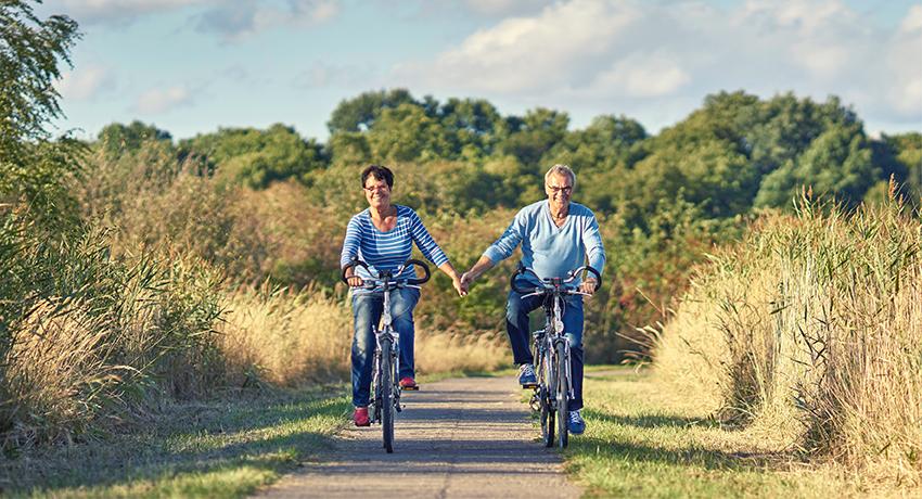 Couple de seniors qui se donnent la main à vélo