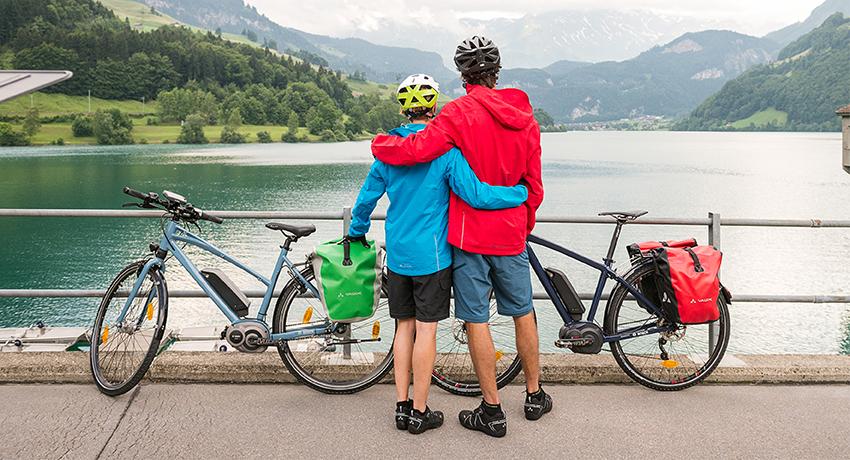 Jeune couple enlacé près de leurs vélos de voyage