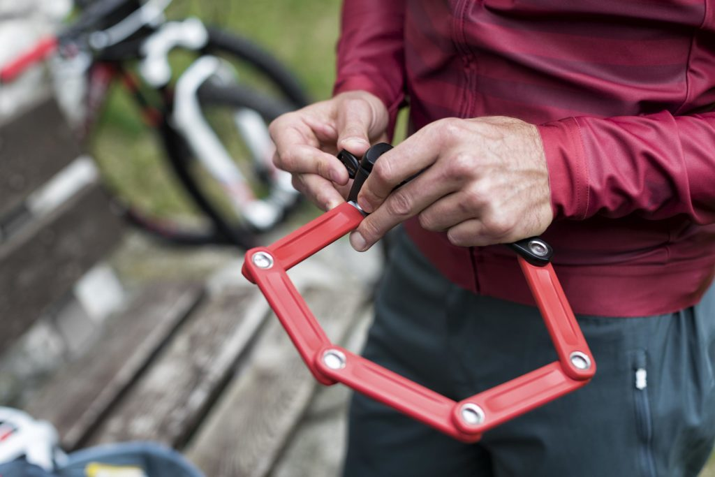 Cycliste qui déplie son antivol pour cadenasser son vélo