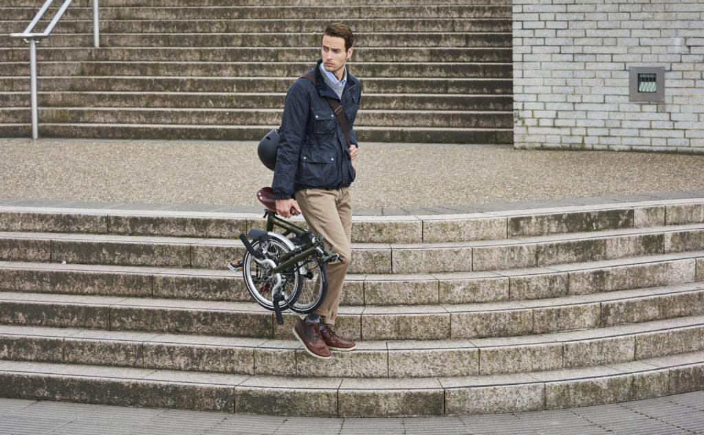Homme portant un vélo Brompton plié dans les escaliers