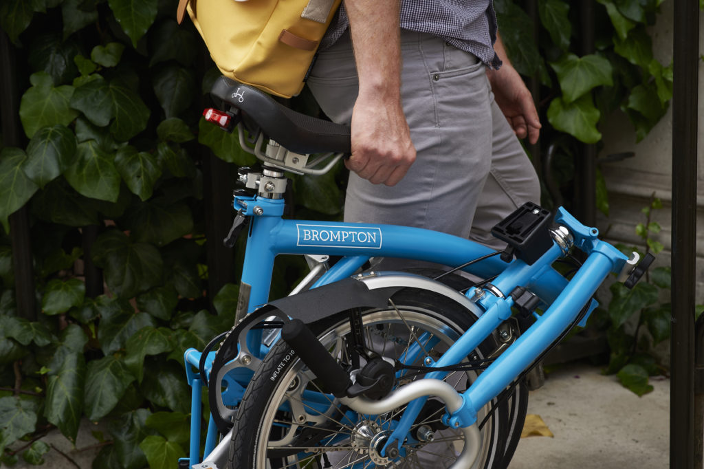 Cycliste qui porte son vélo pliant Brompton plié par la selle
