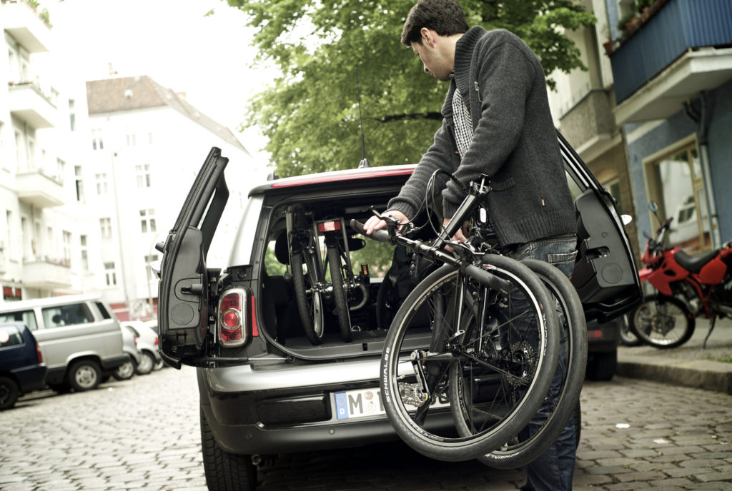 Homme rangeant deux vélos pliables dans le coffre d'une voiture en ville
