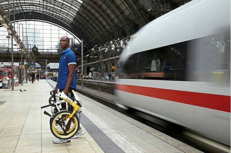 Cycliste sur le quai d'une gare avec son vélo pliant plié à la main