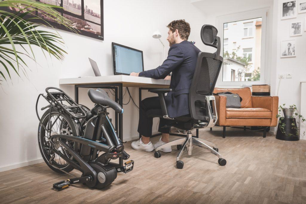 Homme travaillant à son ordinateur avec son vélo pliant plié à côté de son bureau