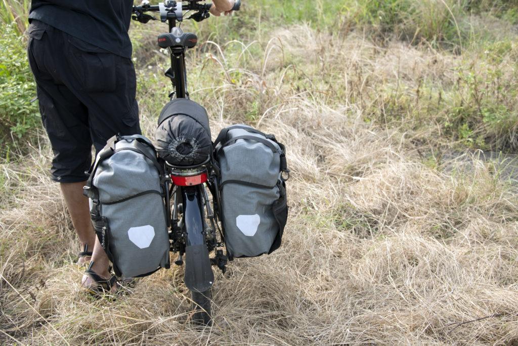 Cyclorandonneur voyageant avec son vélo pliant, sur un chemin de campagne