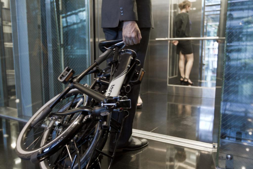Homme qui rentre dans un ascenseur avec son vélo pliant