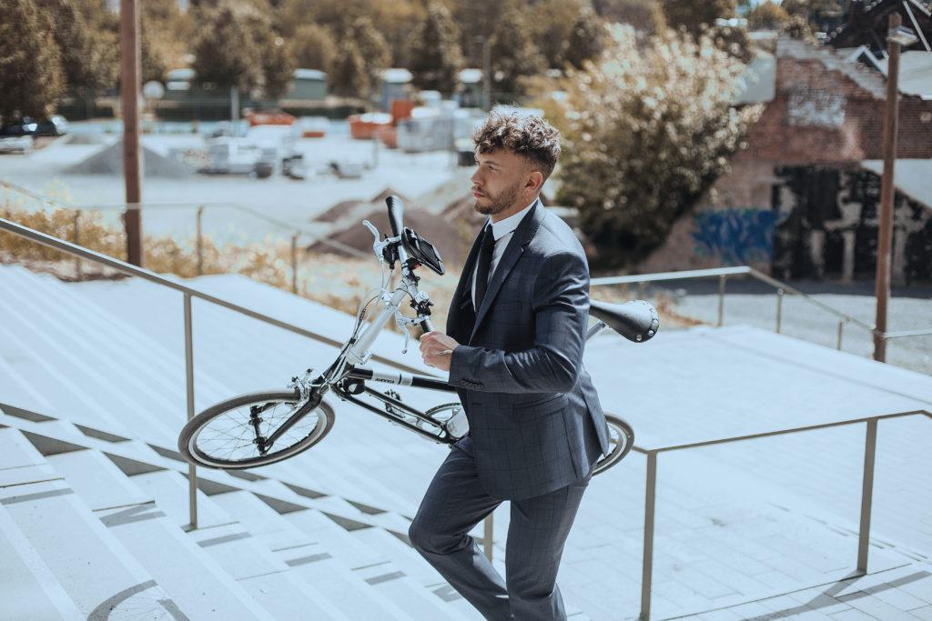 Homme montant les escaliers avec un vélo pliant déplié sous le bras