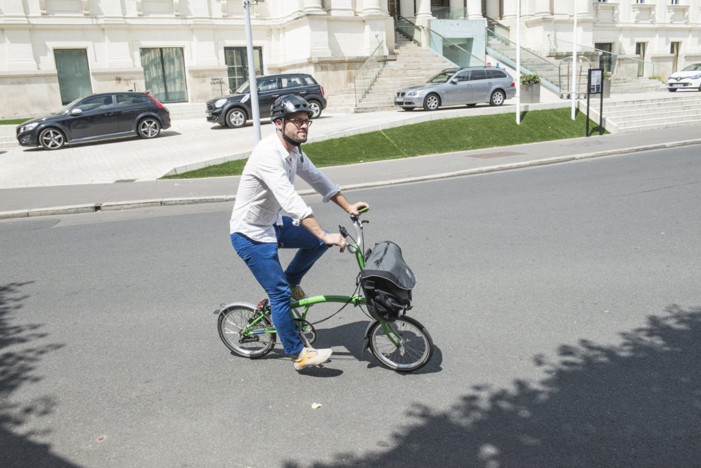 Cycliste sur un vélo pliant Brompton vert avec une sacoche avant