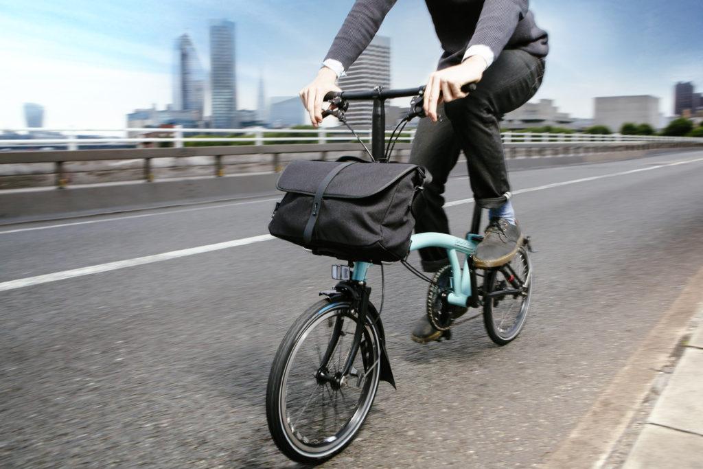 Vélo pliant électrique Brompton Go en train de rouler en ville avec sacoche avant