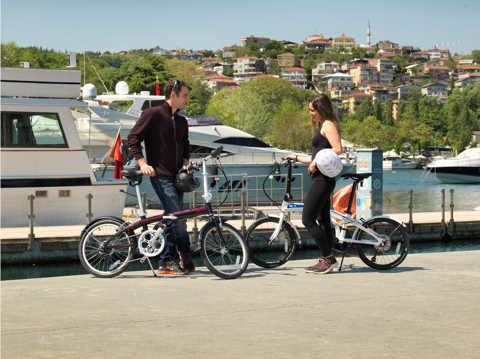 Couple avec des vélos pliants dans un port de plaisance