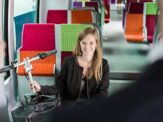 Jeune femme voyageant avec son vélo pliable dans un train SNCF
