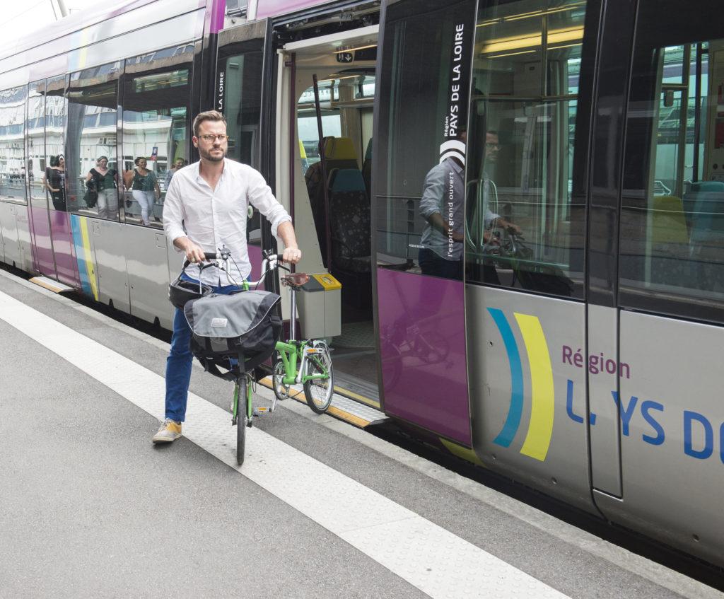 Cycliste qui sort d'un tram avec son vélo pliant déplié