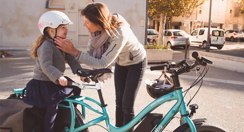 Mère attachant le casque de sa fille sur un vélo cargo Yuba Boda Boda