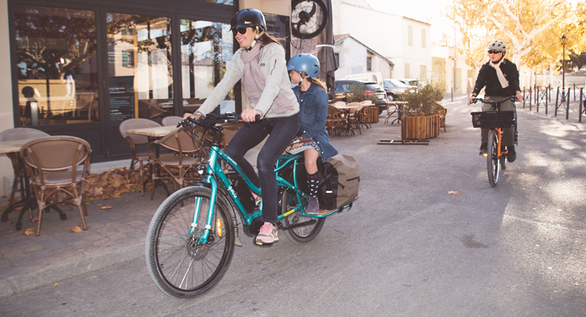 Parents transportant leurs enfants sur des vélos cargos Yuba