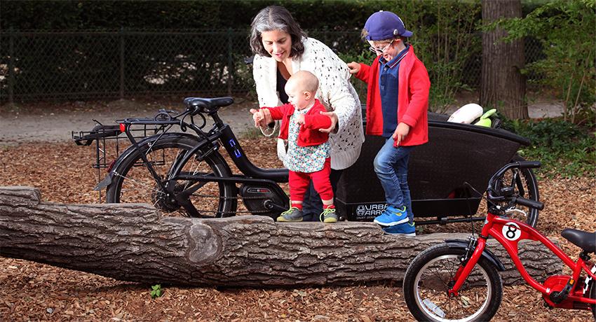 Mère avec ses deux enfants dans la forêt et vélo cargo en fond