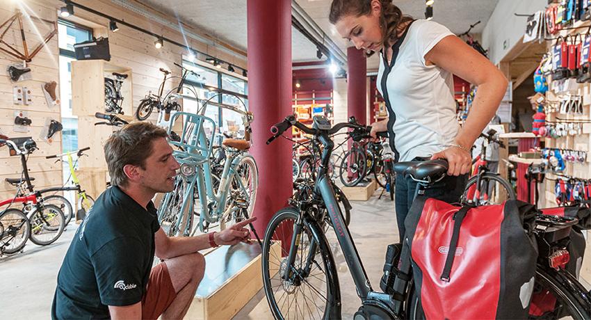Vendeur vélo électrique avec une cliente qui tient un vélo électrique