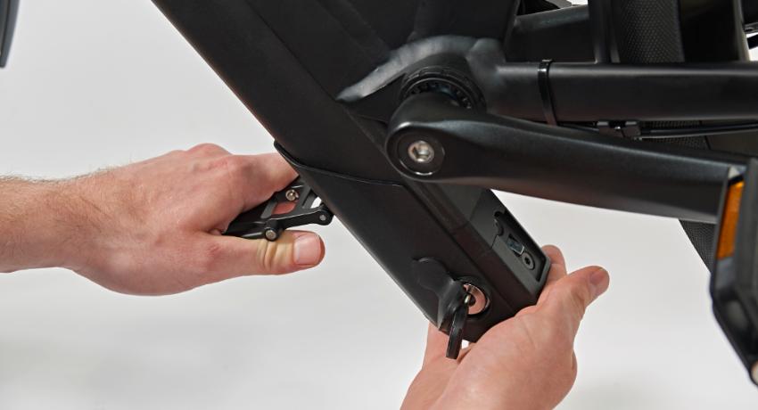 Deux mains opèrent un retrait d'une batterie de vélo électrique