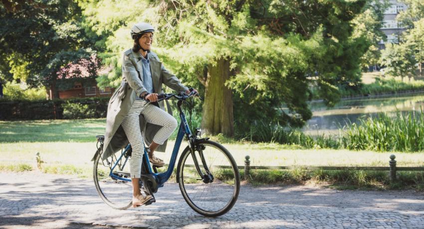 Cycliste femme qui pédale sur un vélo électrique dans un parc