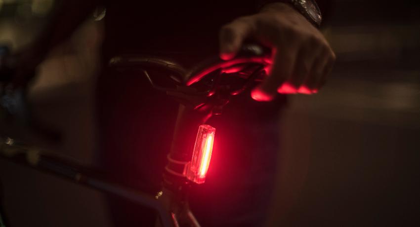 Gros plan sur phare arrière rouge fixé sur la tige de selle d'un vélo