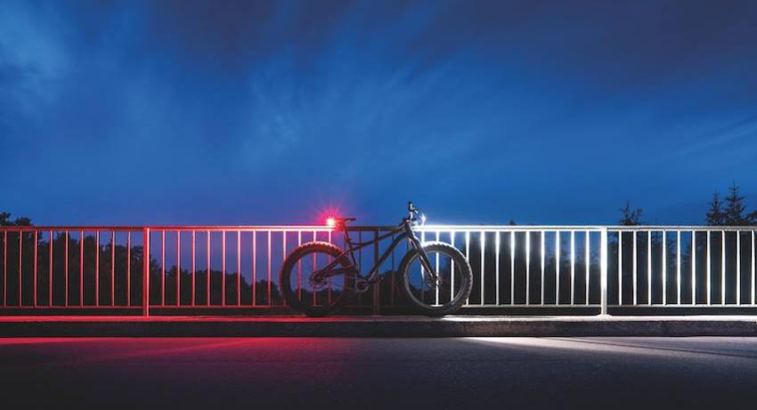 Vélo stationné la nuit avec éclairage blanc à l'avant et phare rouge à l'arrière