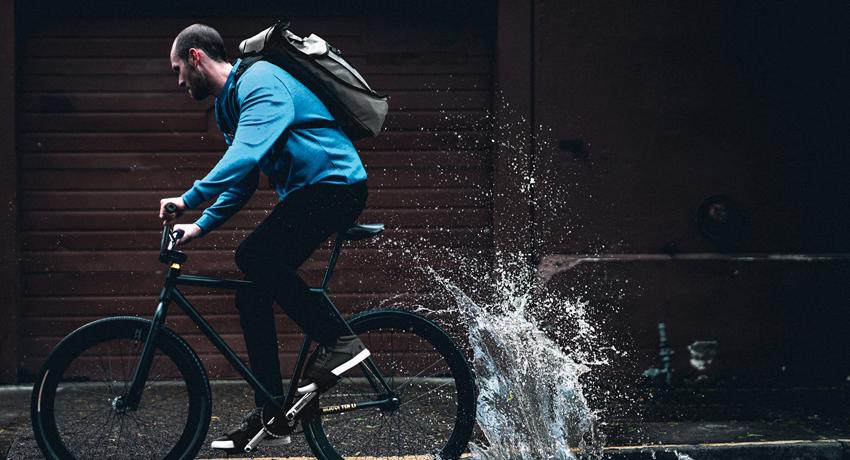 Cycliste roulant dans une flaque avec un sac à dos Chrome