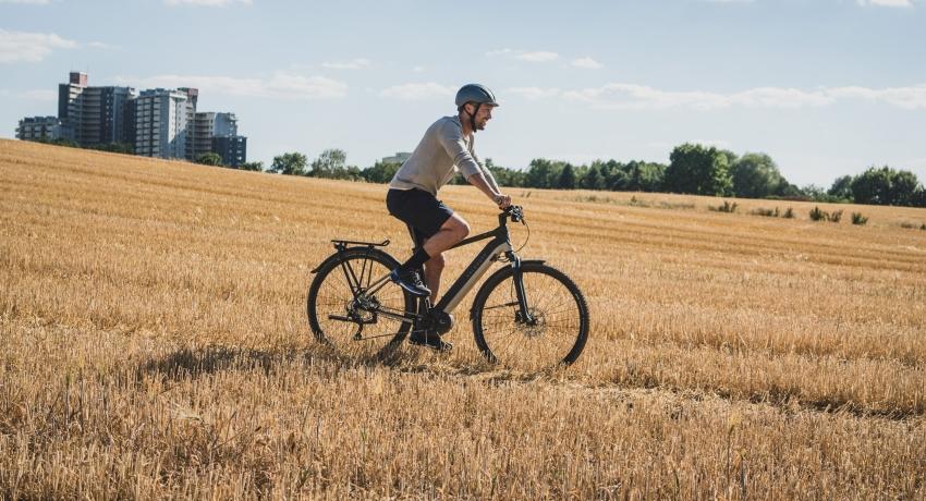 Cycliste roulant dans un champ avec un vélo électrique Kalkhoff Entice 2019