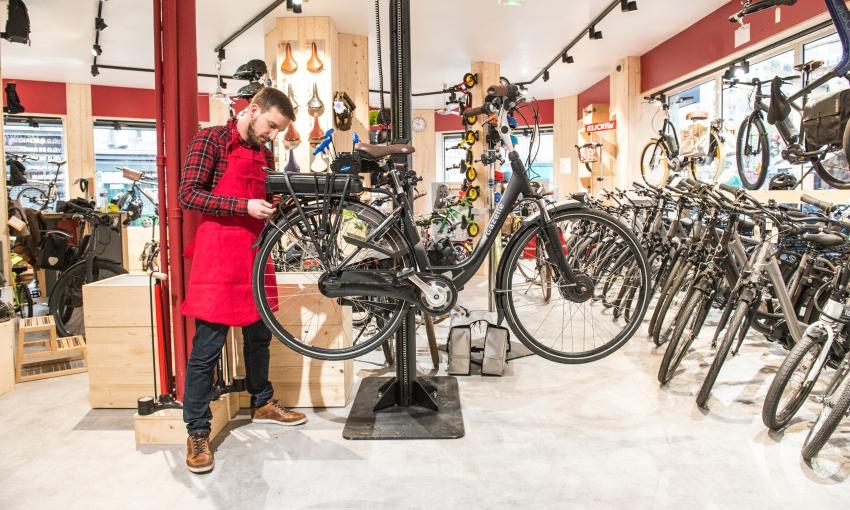 Mécanicien qui fait l'entretien d'un vélo électrique