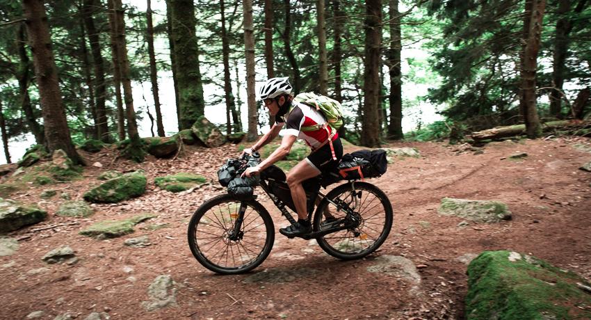 Cycliste sur un vélo gravel tout équipé avec sacoches bikepacking