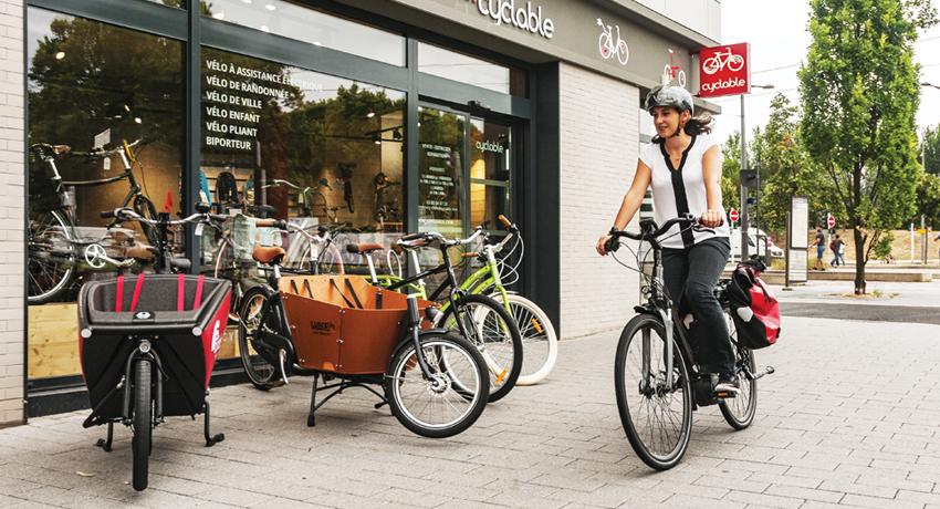 Femme sur un vélo électrique devant un magasin de vélos