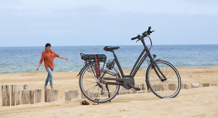 Femme sur une plage avec son vélo électrique trekking
