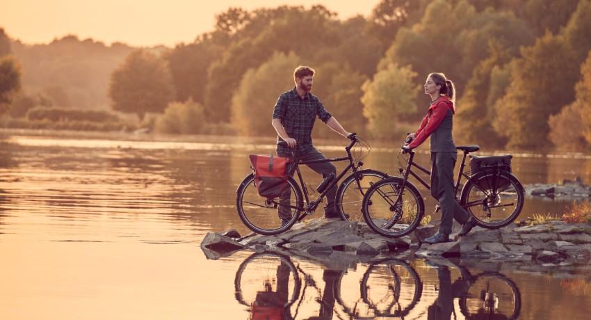 Deux cyclistes arrêtés près d'un lac au coucher du soleil