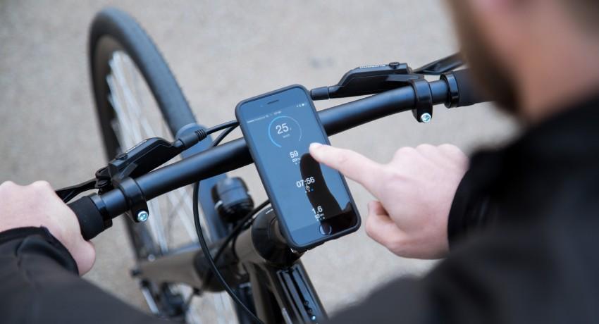 Cycliste manipulant l'application Coboc pour vélo électrique