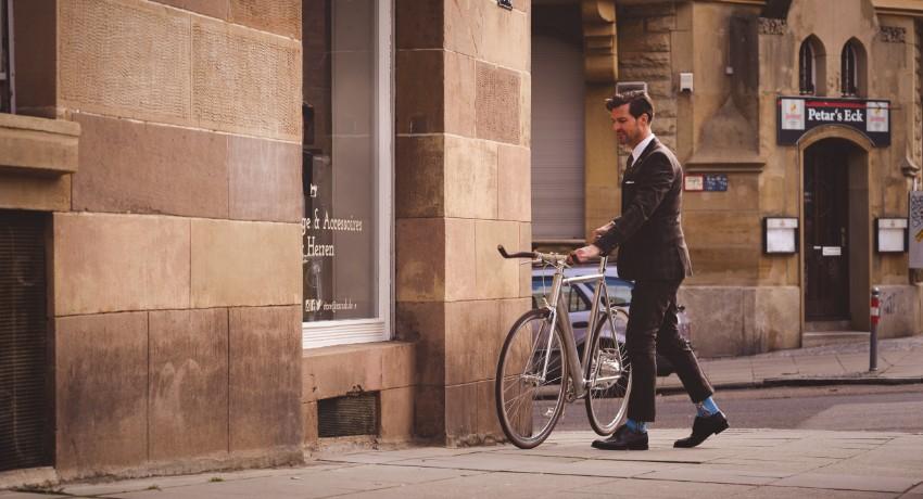 Homme tenant un vélo électrique Coboc Soho en ville