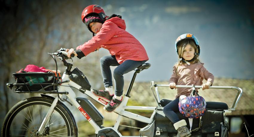 Deux enfants sur un vélo longtail à l'arrêt