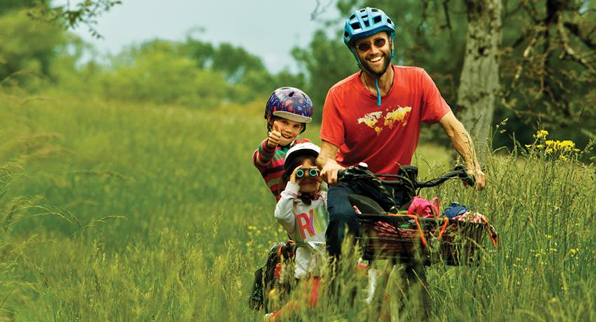 Damien et ses filles dans les prés sur leur vélo cargo