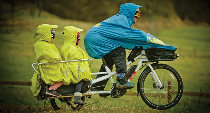 Damien et ses filles sur leur vélo cargo  équipés de ponchos