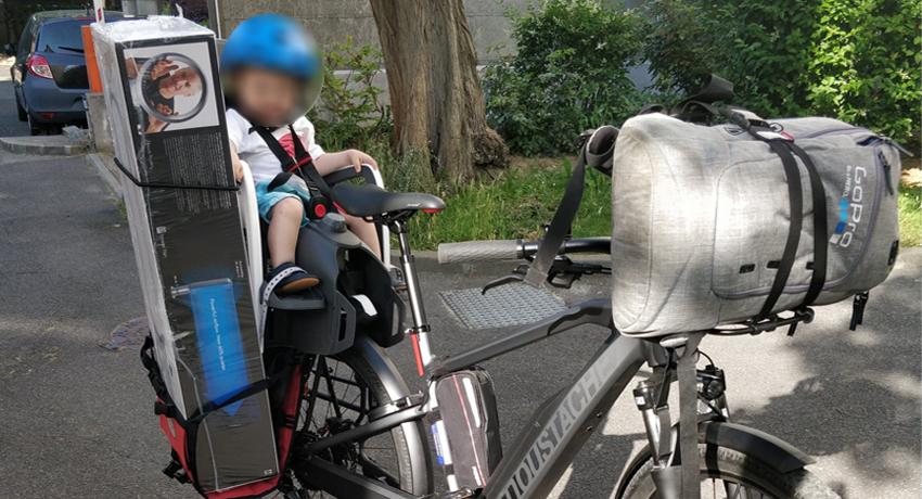 Enfant sur un siège bébé à l'arrêt sur un vélo électrique Moustache
