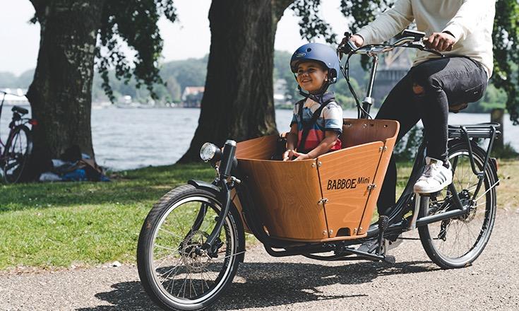 Cycliste et son enfant dans un vélo cargo électrique Babboe