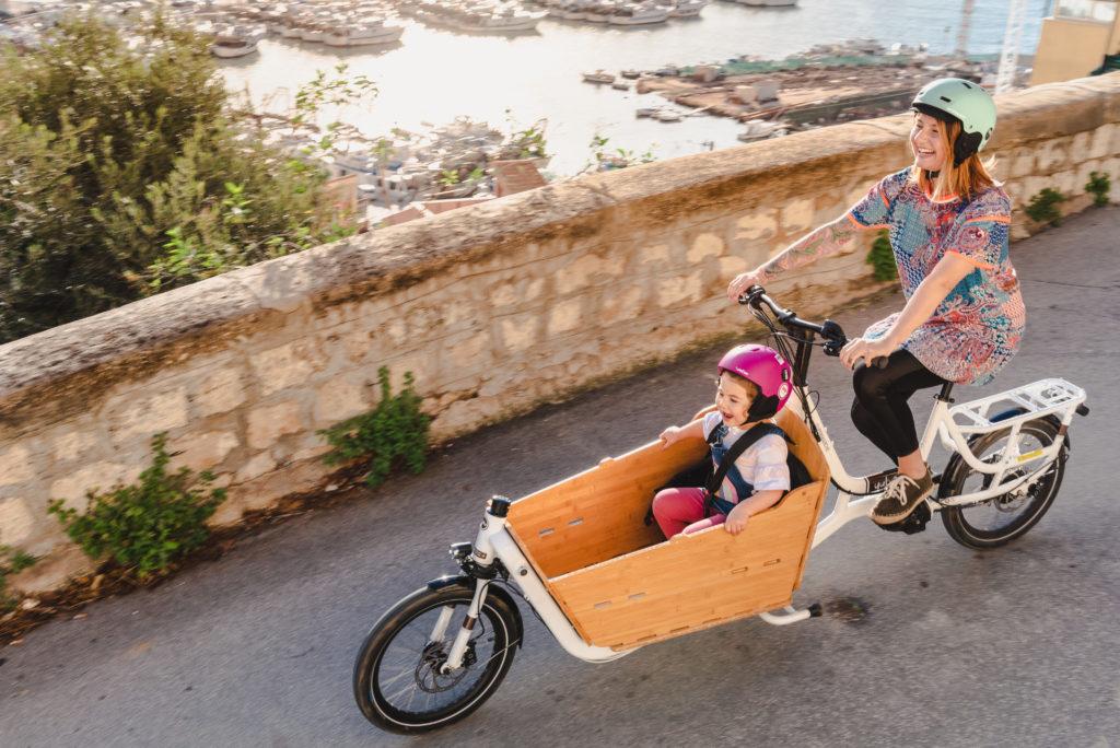 Cycliste sur son vélo cargo avec sa fille, toutes deux souriantes