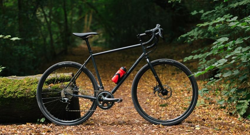 Vélo cadre acier Genesis Crois de Fer dans une forêt