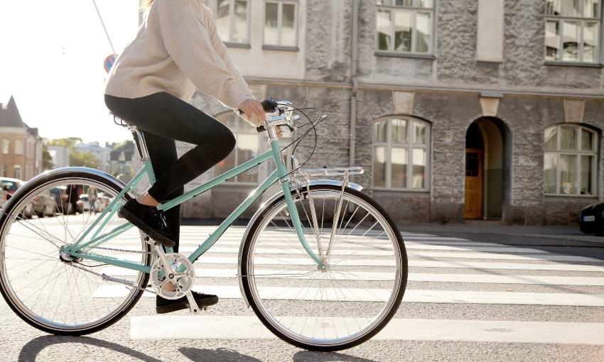 Femme sur un vélo cadre acier en ville