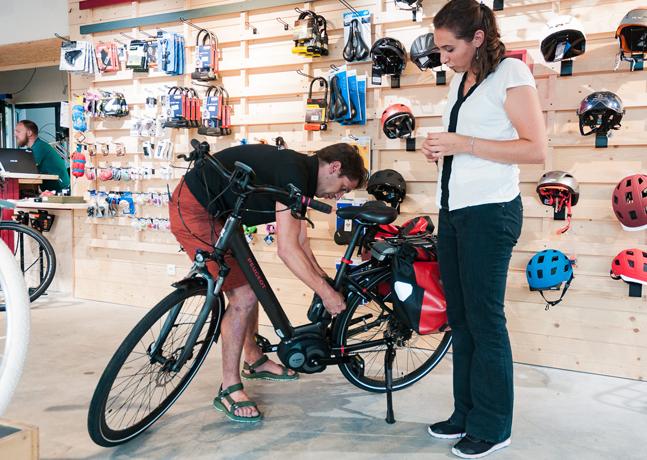 Cycliste dans un magasin de vélo avec un vendeur intervenant sur son vélo électrique